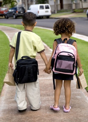 Children Holding Hands While Walking to School