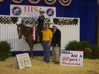 Janelle Lanoue displays the ribbon she won in the Intercollegiate Horse Show Association's national competition in Murfreesboro, Tenn. Also pictured are Tara Swanson, her coach, and Bob Cacchione, IHSA founder.