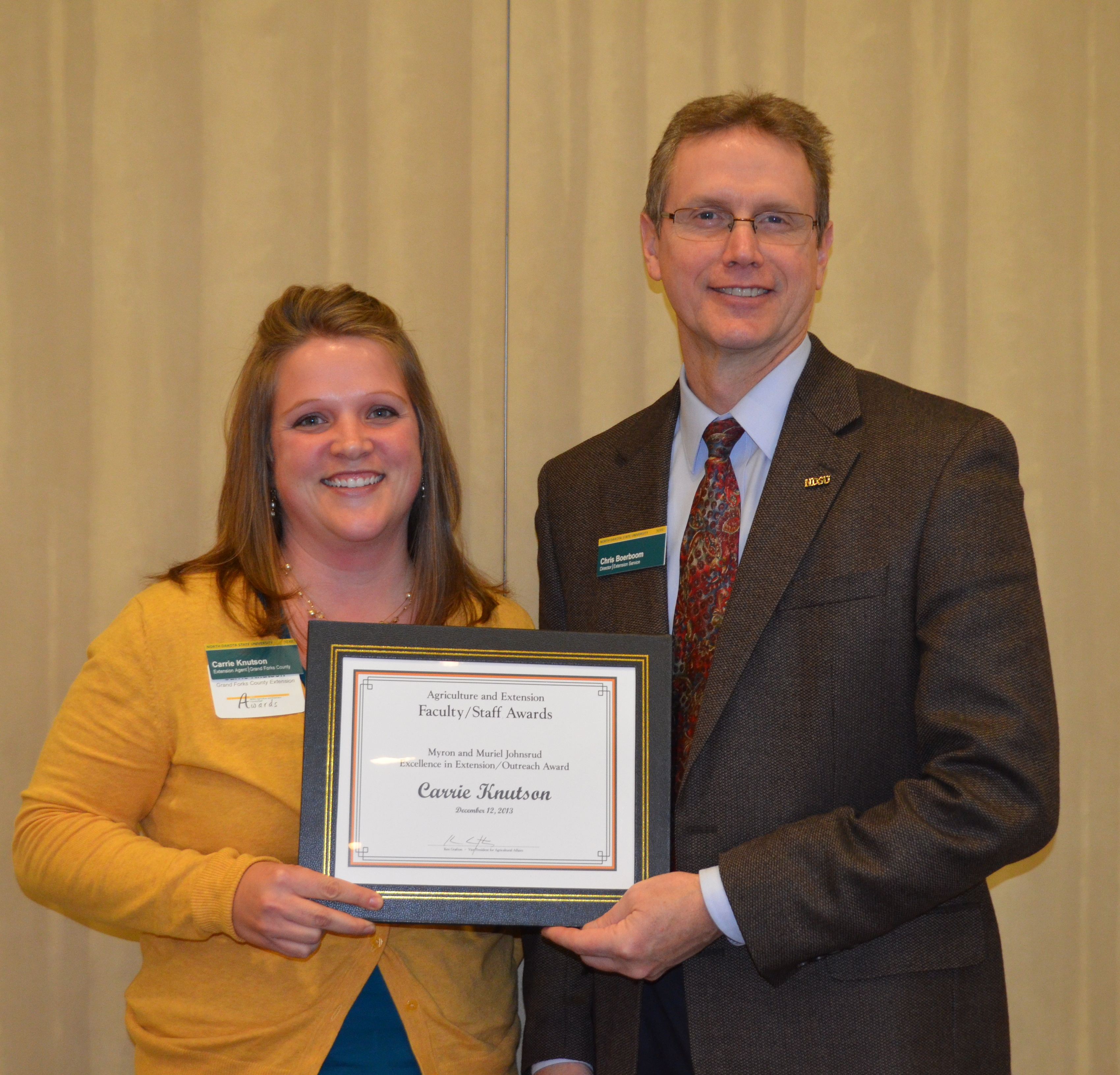 Carrie Knutson, Extension agent, Grand Forks County, receives the Myron and Muriel Johnsrud Excellence in Extension/Outreach Award from Chris Boerboom, director of the NDSU Extension Service.