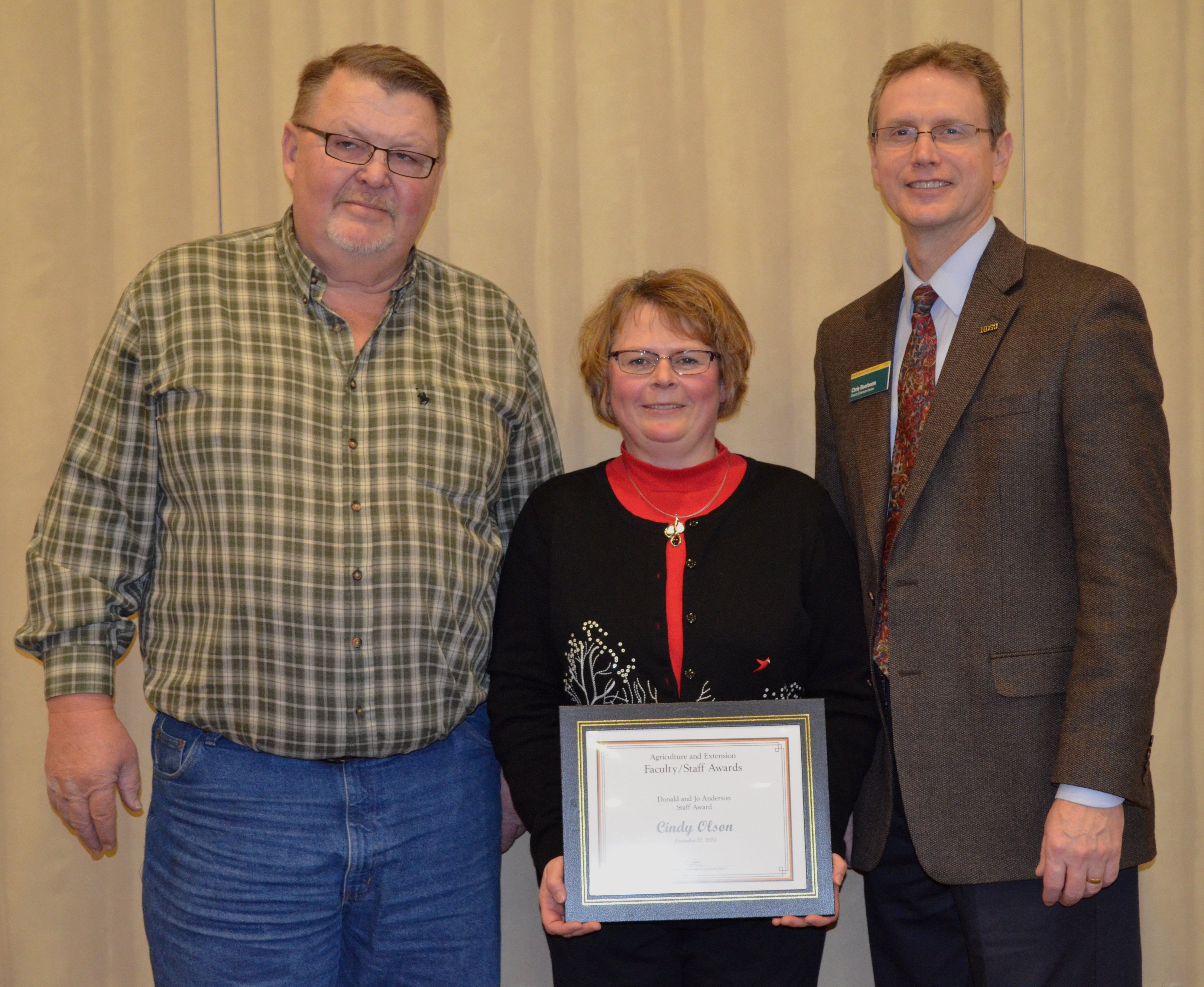 Cindy Olson, administrative assistant, Ramsey County Extension office, receives the Donald and Jo Anderson Staff Award from NDSU Extension Service Director Chris Boerboom, right, with Extension agent Bill Hodous, Ramsey County, at her side.