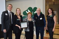 Viola and Chris Leier (center) receive recognition on behalf of their family, which was named a 4-H century family. Those presenting the recognition are (from left) Chris Boerboom, NDSU Extension Service director; Acacia Stuckle, an Extension agent for Emmons County; and Leann Schafer, North Dakota 4-H Foundation Board chair.