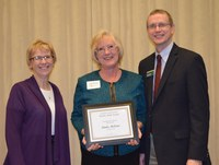Linda McCaw, administrative assistant/conference coordinator/Ag Consortium scheduler, Agriculture Communication (center), receives the Donald and Jo Anderson Staff Award from Chris Boerboom, director of the NDSU Extension Service, and Becky Koch, director of Agriculture Communication.