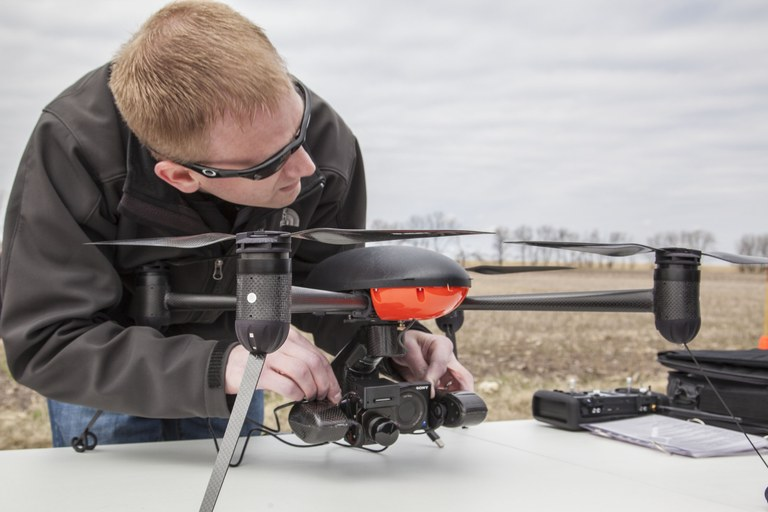 Trevor Woods of the UND Center for Unmanned Aircraft Systems Research, Education and Training is checking the camera on an unmanned aircraft system that's being used in a research project at NDSU's Carrington Research Extension Center. (NDSU photo)