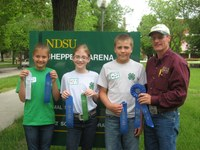 Oliver county team members (from left) Breanna Vosberg, Olivia Klein and Charlie Liffrig, accompanied by their coach, Extension agent Rick Schmidt, show off ribbons they recieved in the junior division of the 4-H dairy judging contest at NDSU.