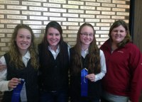 Members of the Ward County 4-H hippology team display the ribbons they received for taking first place in the senior division of the hippology contest at the North Dakota Winter Show. Pictured  (from left) are team members Shaylee Miller, Parker Bush and Kara Scheresky, and coach Paige Brummund. (Not pictured is team member Lindsey Sys.)
