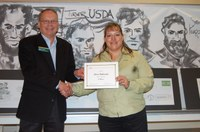 Randy Mehlhoff, Langdon Research Extension Center dirctor, presents the award to Lisa Pederson.