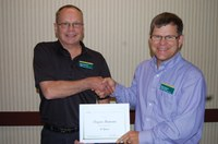 Randy Mehlhoff, Langdon Research Extension Center director (left), presents the award to Bryan Hanson.
