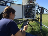 Barb Mullins, NDAWN data acquisition manager, doing maintenance on weather station equipment.