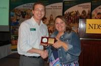 Association for Communication Excellence state representative Scott Swanson congratulates Mary Berg, the 2015 Communicator of Achievement. (NDSU photo)