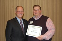 NDSU Sheep Unit manager Skip Anderson, right, receives the Charles and Linda Moses Staff Award during the 25th annual Agriculture and Extension Faculty/Staff Awards program Dec. 8. Also pictured is NDSU President Dean Bresciani. (NDSU photo)