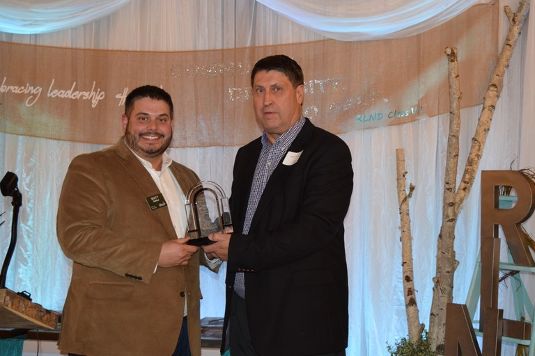 RLND Council chairman Mike O'Keeffe, right, presents Matt Dahlke, loan officer for Farm Credit Services of Mandan, with the RLND Champion Award that FCSM was honored with during the RLND Class VII graduation gala. (NDSU photo)