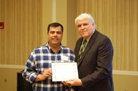 Juan Osorno, left, receives the Larson/Yaggie Excellence in Research Award from David Buchanan, associate dean for academic programs. (NDSU photo)