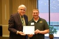 Thomas Brown, right, receives the Rick and Jody Burgum Staff Award from David Buchanan, associate dean for academic programs. (NDSU photo)