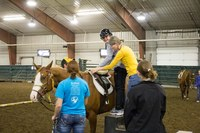 Erika Berg, NDSU associate professor and Bison Strides director, helps a girl mount a horse for her Equine-assisted Activities and Therapies program lesson. (Photo courtesy of Healthcare Equipment Recycling Organization of Fargo)