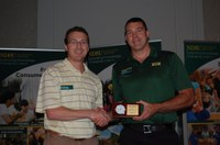 Sam Markell (right) receives the Communicator of the Year Award from Scott Swanson, NDSU Agriculture Communication electronic media specialist and representative of the Association for Communication Excellence's North Dakota chapter. (NDSU photo)