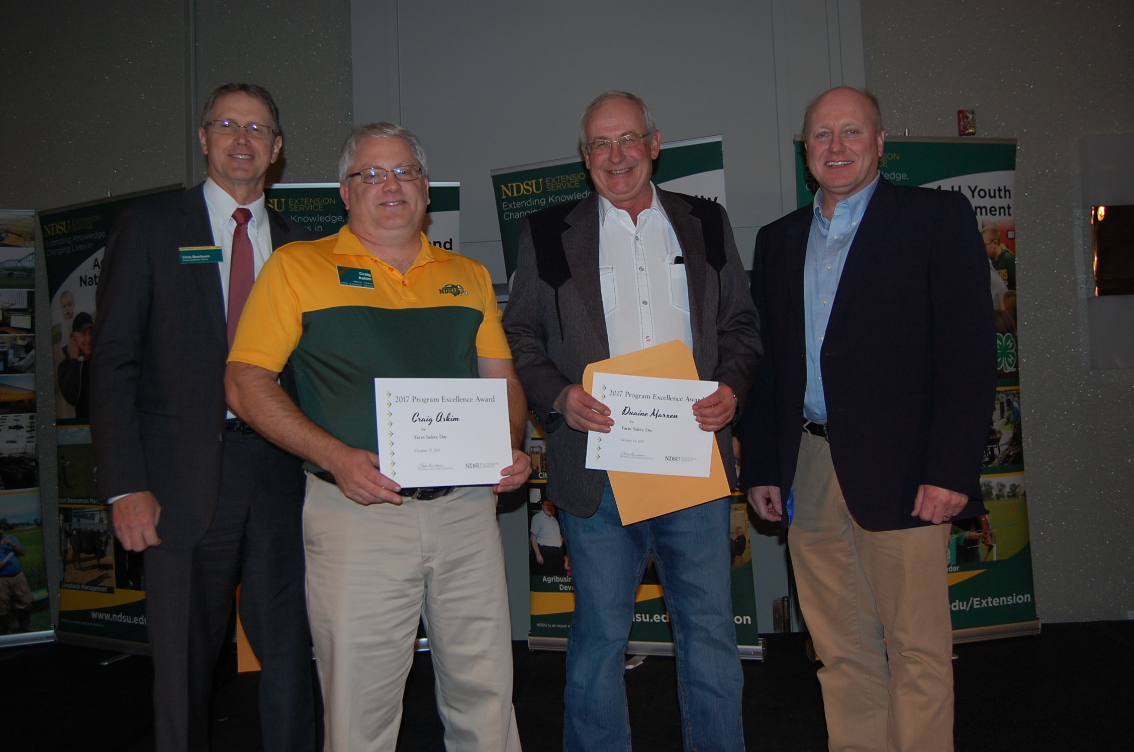 Extension agents Craig Askim, Mercer County (second from left), and Duaine Marxen, Hettinger County, receive a Program Excellence Award for Farm Saftey Day from NDSU Extension Director Chris Boerboom, left, and Jim Murphy, Farm and Ranch Guide (far right). (NDSU photo)