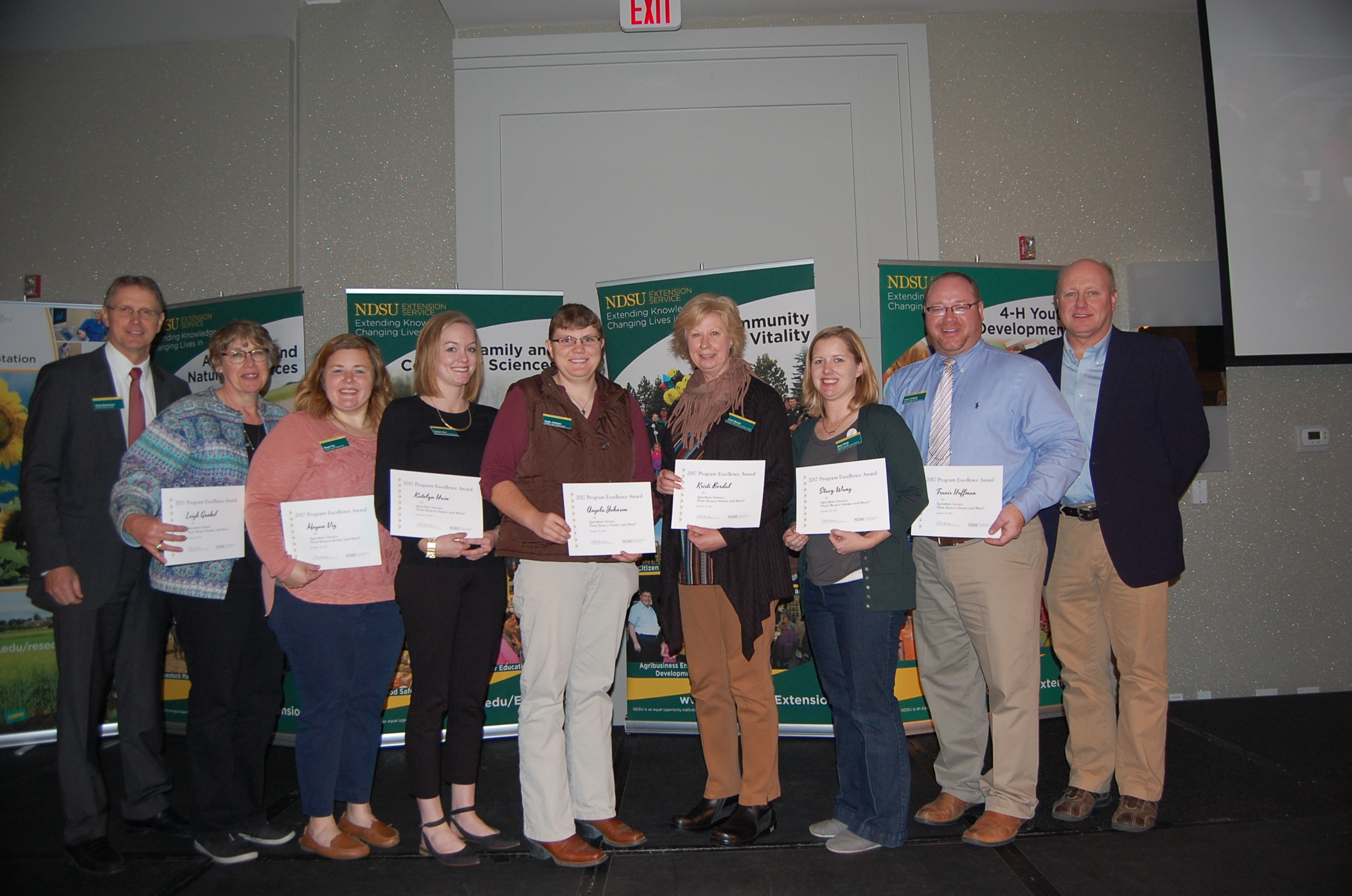 The Sheep to Sweater (and More) team receives a Program Excellence Award. Pictured are (from left): NDSU Extension Director Chris Boerboom; agent Leigh Gunkel, Griggs County; agent Megan Vig, Griggs County; agent Katelyn  Hain, Nelson County; agent Angie Johnson, Steele County; agent Kristi Berdal, Nelson County; Stacy Wang, Extension associate; Travis Hoffman, Extension sheep specialist; and Jim Murphy, Farm and Ranch Guide. (NDSU photo)