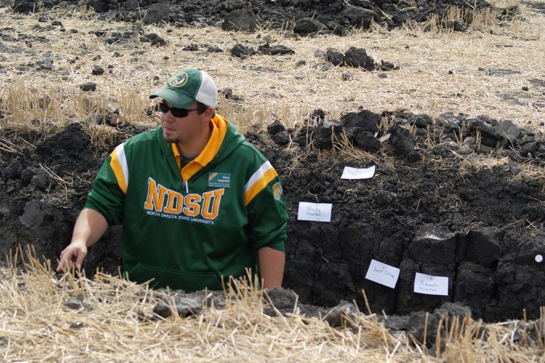 NDSU Extension soil health specialist Chris Augustin explains what is happening in the soil at this demonstration pit. (NDSU photo)