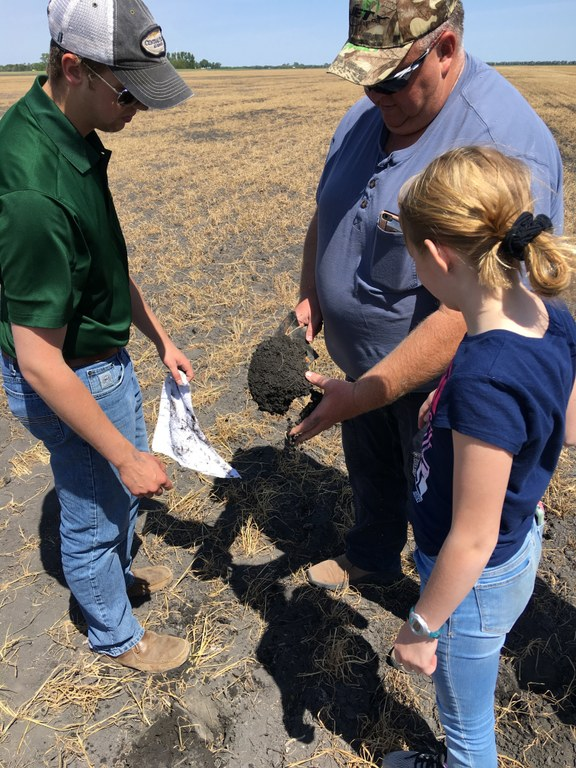 NDSU soil health technician Luke Ressler (left) helps a producer and his daughter estimate the soil health on their farm. (NDSU photo)