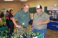 Tom Peters, NDSU Extension sugar beet agronomist (center), talks to a visitor about weeds during a Big Iron Farm Show. (NDSU photo)