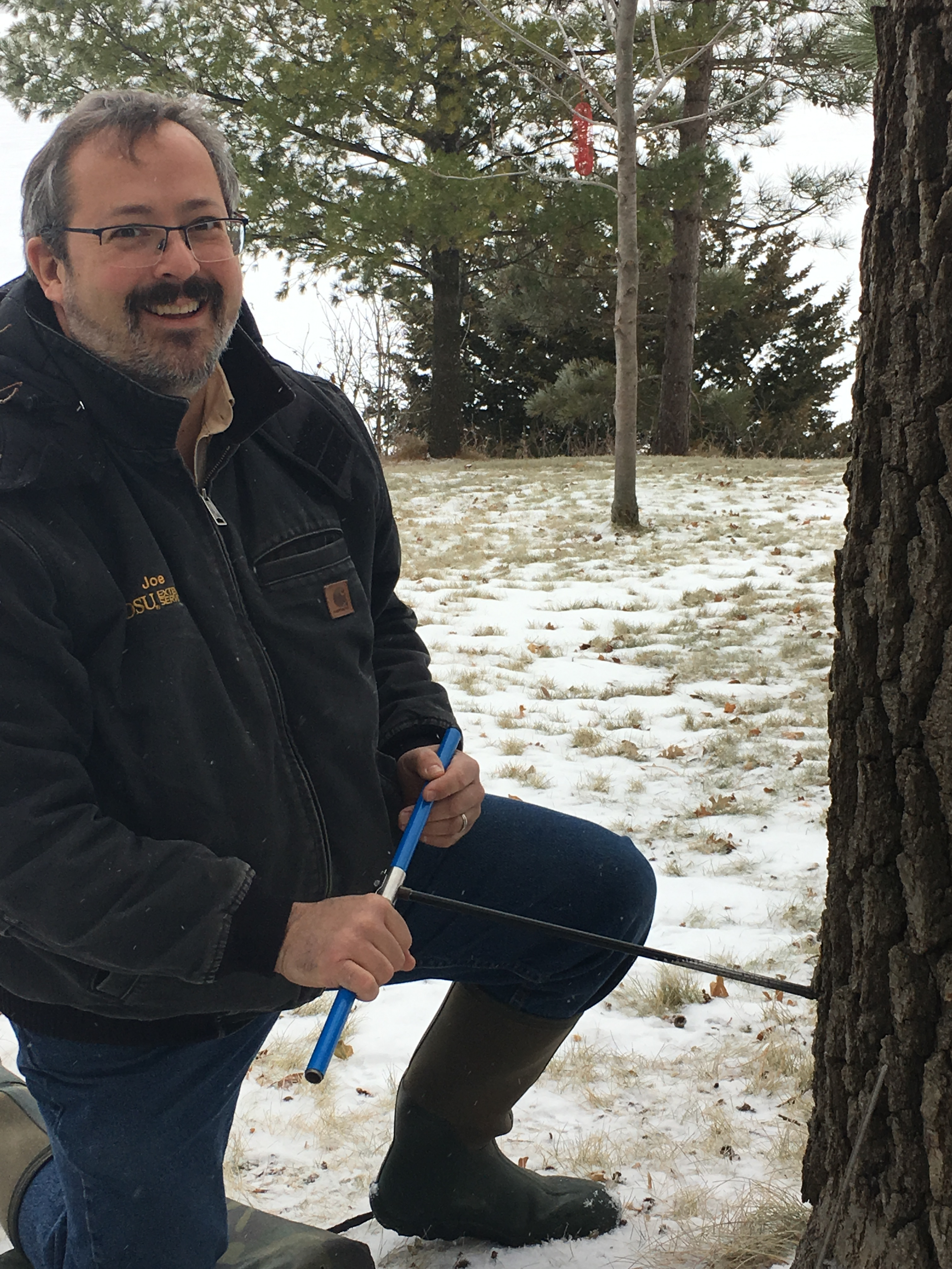NDSU Extension forester Joe Zeleznik collects a sample from a bur oak along the Red River. (NDSU photo)