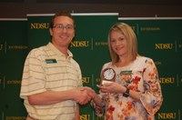 Miranda Meehan, NDSU Extension livestock environmental stewardship specialist, receives the 2018 Communicator of the Year award from Scott Swanson, NDSU Agriculture Communication electronic media specialist and state representative for North Dakota's chapter of the Association for Communication Excellence. (NDSU photo)