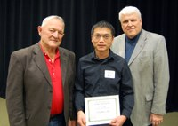 Zhaohui Liu, center, receives the Larson/Yaggie Excellence in Research Award from Robert Yaggie, left, and David Buchanan, associate dean for academic programs. (NDSU photo)