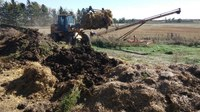 Adding cover material such as straw or old hay is the last step in creating a compost pile or windrow for disposing of dead livestock. (NDSU photo)
