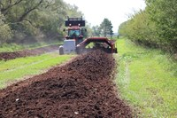 Compost is being turned at the Carrington Research Extension Center as part of a demonstration day. (NDSU photo)