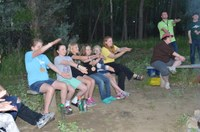 Youth and counselors sing a campfire song while at the North Dakota 4-H Camp near Washburn. (NDSU photo)
