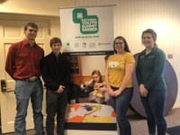 North Dakota 4-H'ers who attended the 4-H Youth AgriScience Summit stand in front of a poster promoting the summit. Pictured are (from left) Mitch Stuber, Noah Helgoe and Haley Cowan, and chaperone Sarah McNaughton. (NDSU photo)