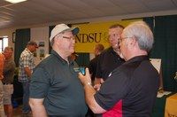 Ken Hellevang, NDSU Extension agricultural engineer (left), talks to visitors at the Big Iron farm show. (NDSU photo)