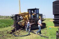 Workers connect tile to a plow. (NDSU photo)