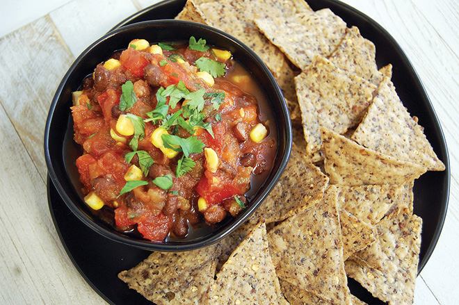 corn and black bean salsa in bowl surrounded by whole-grain crackers