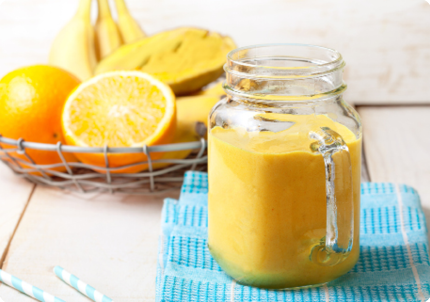 glass of orange juice with bowl of fruit