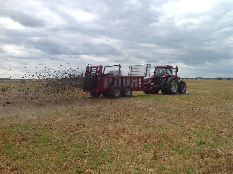 a tractor with spreader turned on