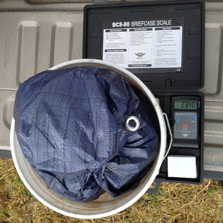 a plastic sheet containing manure on a scale