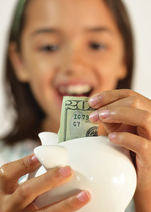 girl putting $20 bill in piggy bank