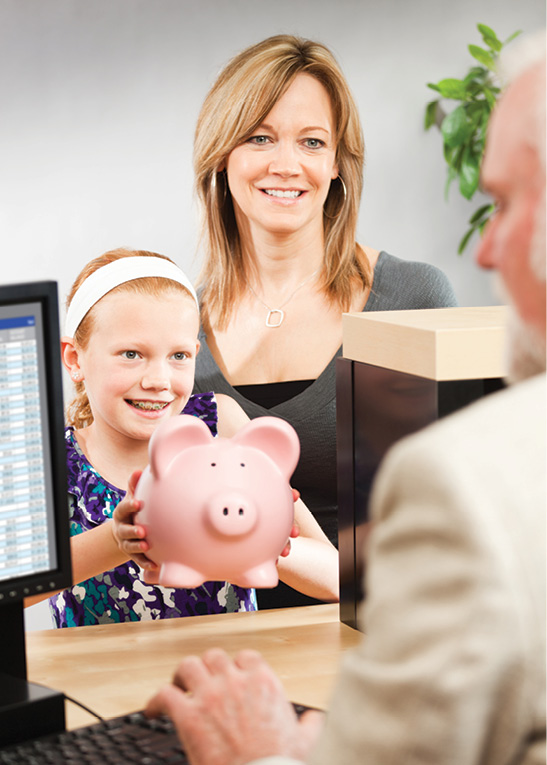 mom and daughter with piggy bank at a bank teller's window